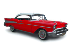 Classic red car with polished chrome trim, on a white background